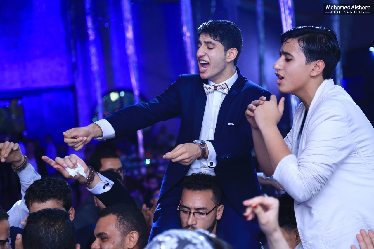 young men, men, lifestyles, young adult, enjoyment, togetherness, leisure activity, young women, arts culture and entertainment, illuminated, night, indoors, standing, women, cheerful, happiness, nightlife, well-dressed, large group of people, smiling, nightclub, audience, adult, people
