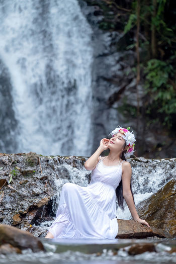 A beautiful young lady relaxes in nature near a waterfall.
