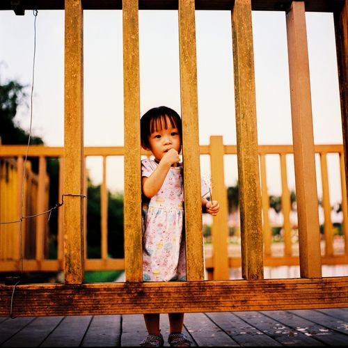 Portrait Of Girl Standing On Boardwalk Seen Through Wooden Railing