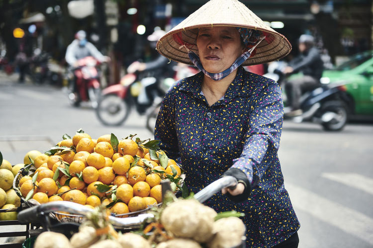 Midsection of woman with fruits on street in city