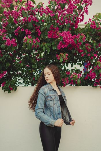 Teenager girl standing by wall with flowering plants outdoors