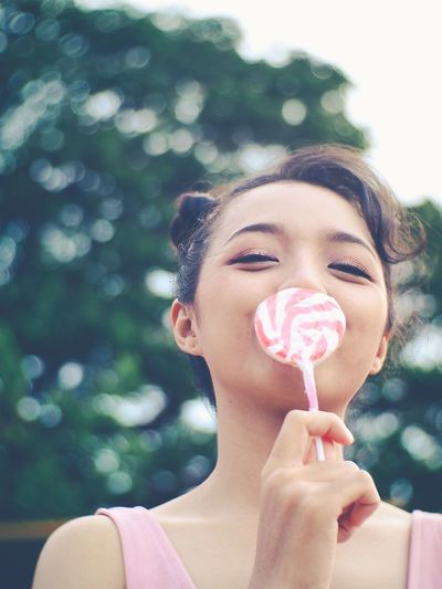 Portrait of woman holding lollipop