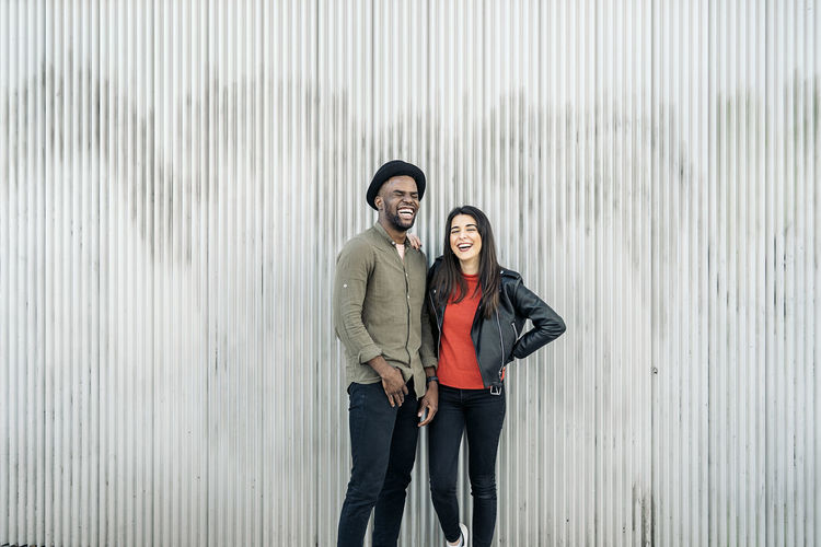 Laughing young couple standing against wall