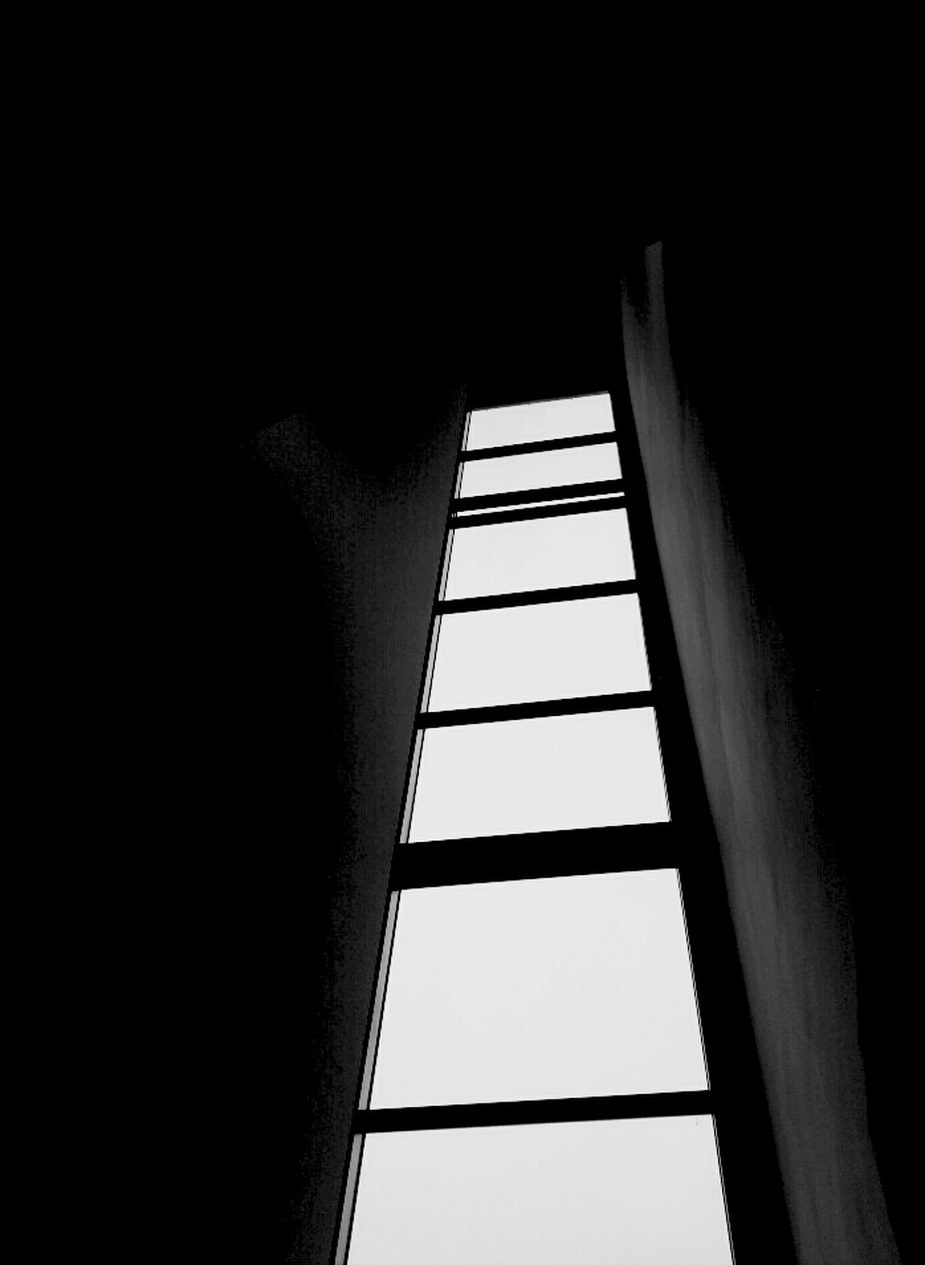 low angle view, indoors, built structure, architecture, clear sky, dark, copy space, window, sunlight, no people, day, silhouette, building, shadow, wall, part of, directly below, close-up, wall - building feature, sky