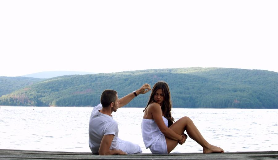 Young Couple Sitting On Pier Against Lake