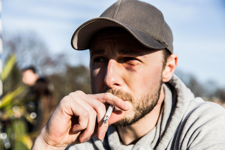 Close-Up Of Young Man Smoking Cigarette Outdoors