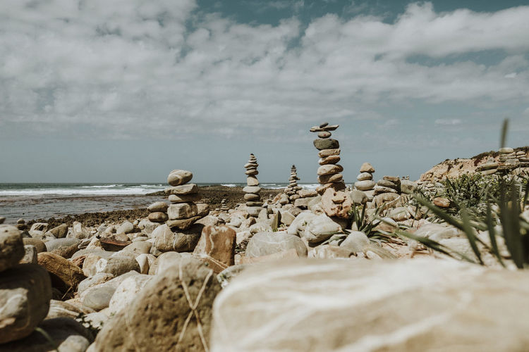 Stones stacked at beach against sky