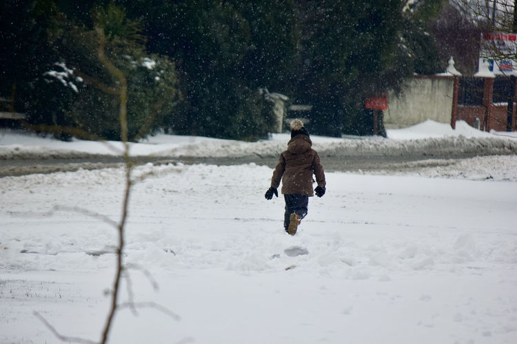 Full length rear view of boy walking on snow