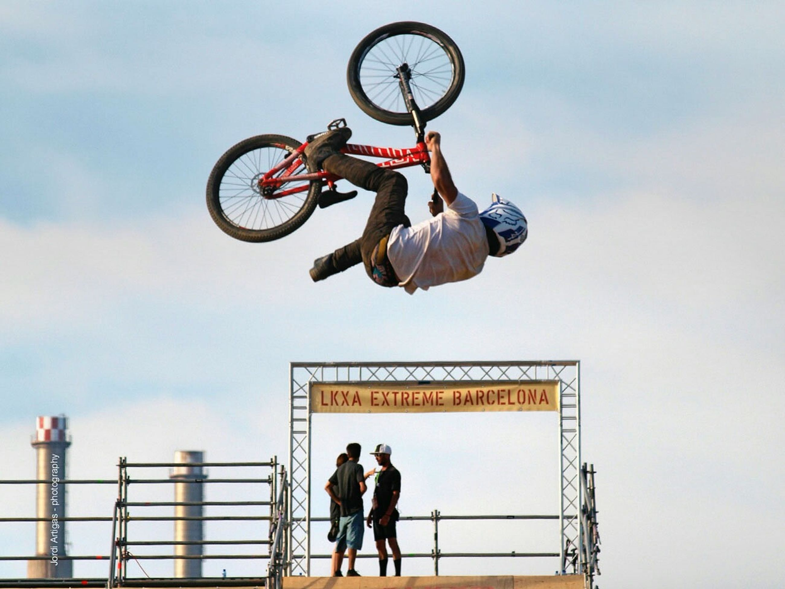 lifestyles, men, leisure activity, communication, text, sky, full length, low angle view, bicycle, transportation, western script, risk, stunt, sport, holding, extreme sports, standing