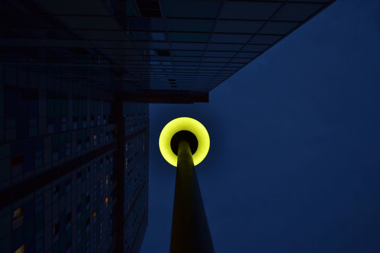 Lamp post by building against clear sky