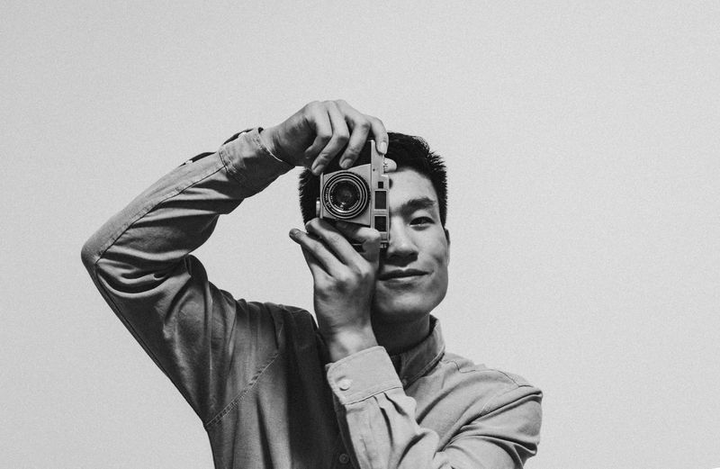 Portrait of young man photographing from camera against gray background