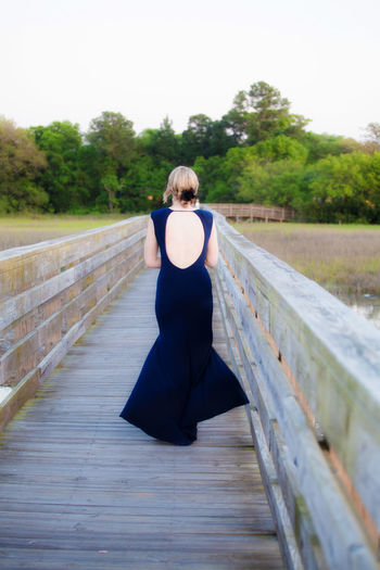 A woman walking on a dock in Folly Beach, South Carolina during a wedding reception. Backless Dress Dock Dressed Up Fence Lifestyles Perspective Railing Walking Wedding Reception Wood Wood - Material Photography In Motion