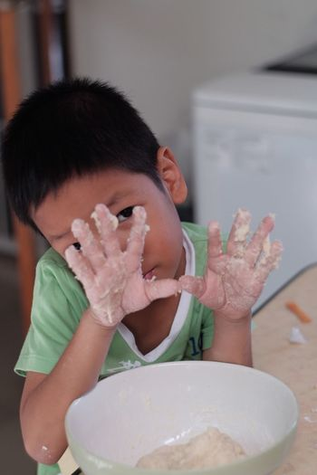 Portrait of boy holding ice cream in bowl on table