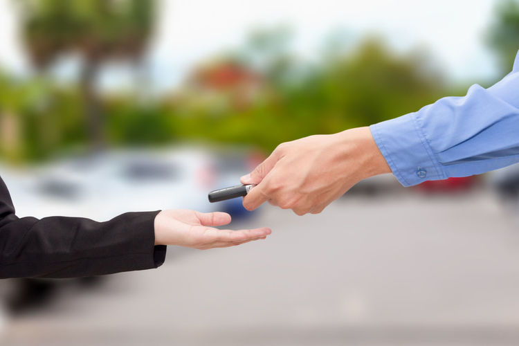 Cropped hand giving car key to female customer