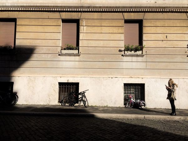 Architecture Building Exterior Built Structure Real People Outdoors Full Length Bike Women Men Baby Stroller Day Light And Shadow Adult People The City Light Mobile Conversations The Street Photographer - 2017 EyeEm Awards Adventures In The City Visual Creativity The Street Photographer - 2018 EyeEm Awards My Best Travel Photo