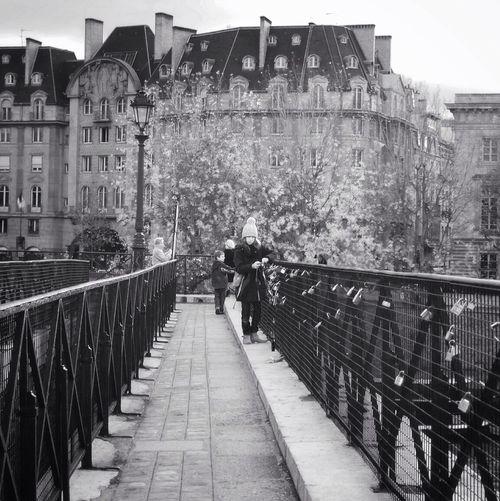 Girl Walking On Elevated Walkway Against Buildings In City