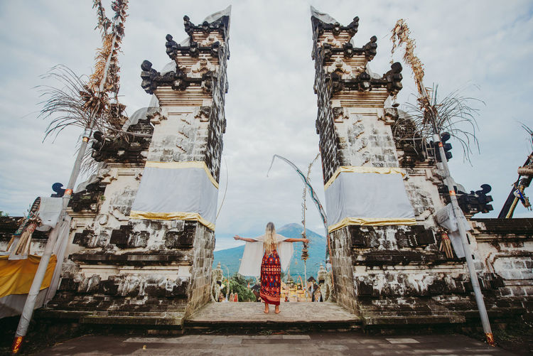 Young woman standing at temple gate