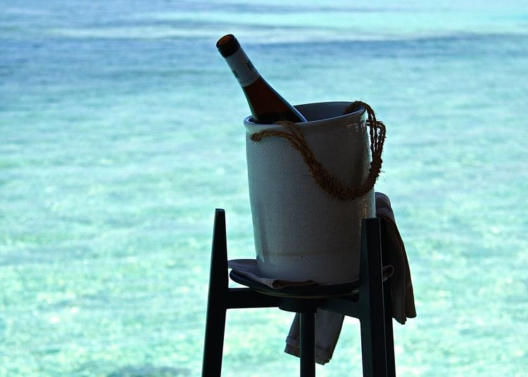 Wine bottle in container by sea