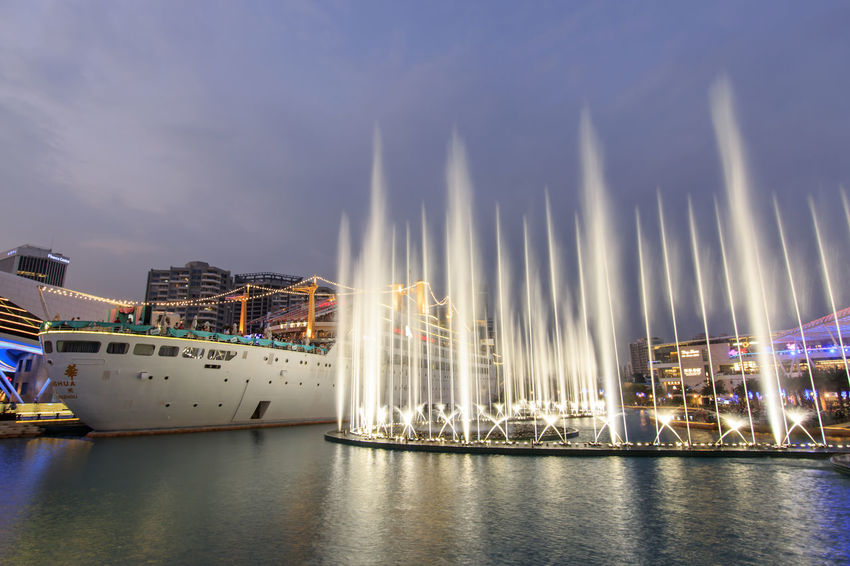 "Shenzhen, China - August 22,2015: Dancing Fountains in New Sea World Plaza, one of the landmark of Shenzhen, at sunset with the Minghua ship on its center. The ship was originally known as Anceevilla and was later renamed ""Minghua"" by the chinese who bought it. Anceevilla ASIA Boat China City City Life Cloud Cloud - Sky Cloudy Dancing Fountain Guandong City Harbor Illuminated Mast No People Outdoors Sailboat Shenzhen Shenzhen.China Sky Stock Market Tourism Travel Destinations Water Waterfront"