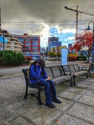 Rear view of woman sitting on sidewalk in city