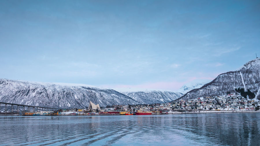 Scenic view of Tromsø Fjord Arctic Architecture Beauty In Nature Cold Temperature Lake Mode Of Transportation Mountain Peak Mountain Range Nature Nautical Vessel No People Outdoors Scenics - Nature Sky Snow Snowcapped Mountain Transportation Water Waterfront Winter
