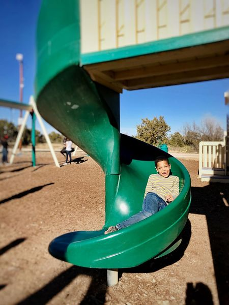 Playground Fun Green Playground Slide Playground Childhood Looking At Camera One Person Outdoor Play Equipment Smiling Happiness Casual Clothing Leisure Activity Real People Sitting Day Portrait Lifestyles Full Length Elementary Age Fun Outdoors Boys Enjoyment