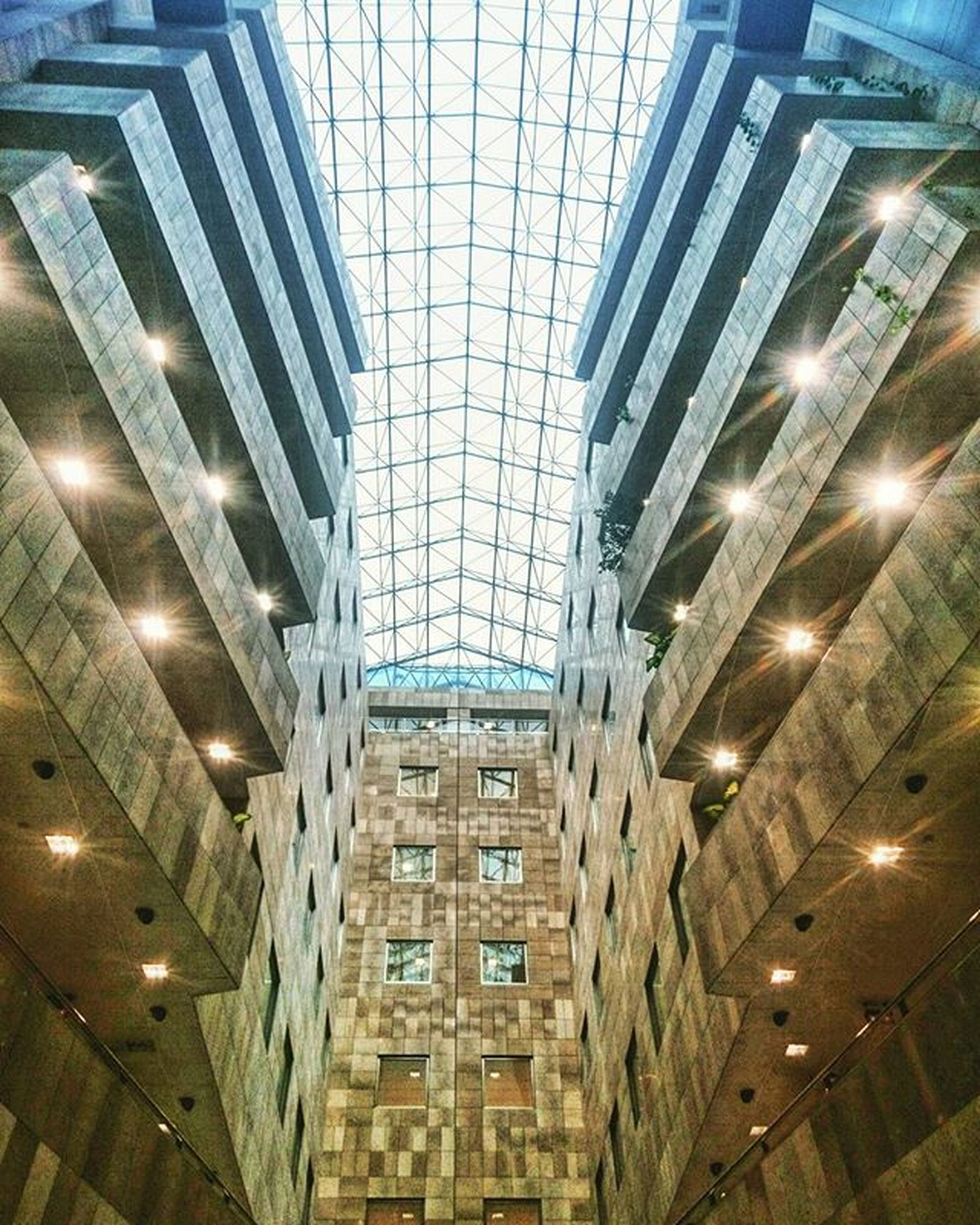 architecture, built structure, ceiling, indoors, low angle view, illuminated, modern, building exterior, building, pattern, lighting equipment, glass - material, architectural feature, no people, city, window, design, in a row, repetition, office building