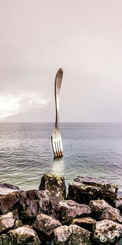 Digital Composite Image Of Large Fork On Sea Against Sky