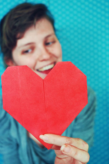 Smiling young woman holding heart shape paper