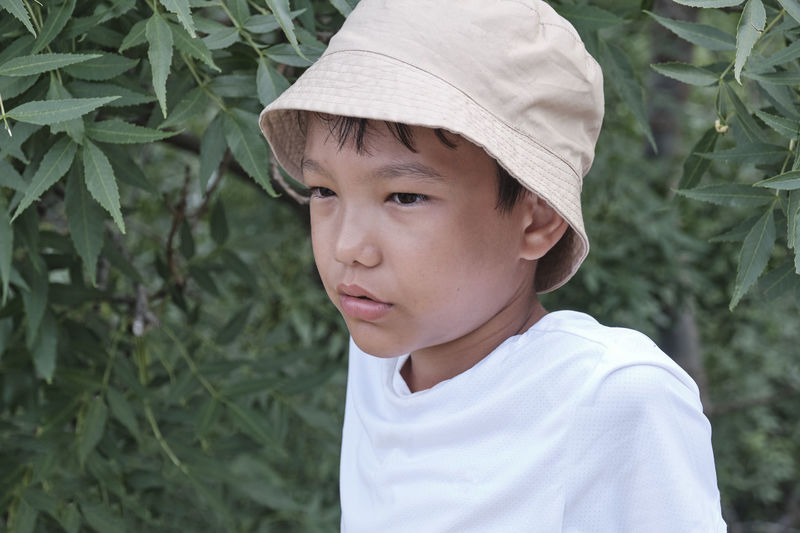 Close-up portrait of an asian boy in a white t-shirt and a panama hat on a background of nature.