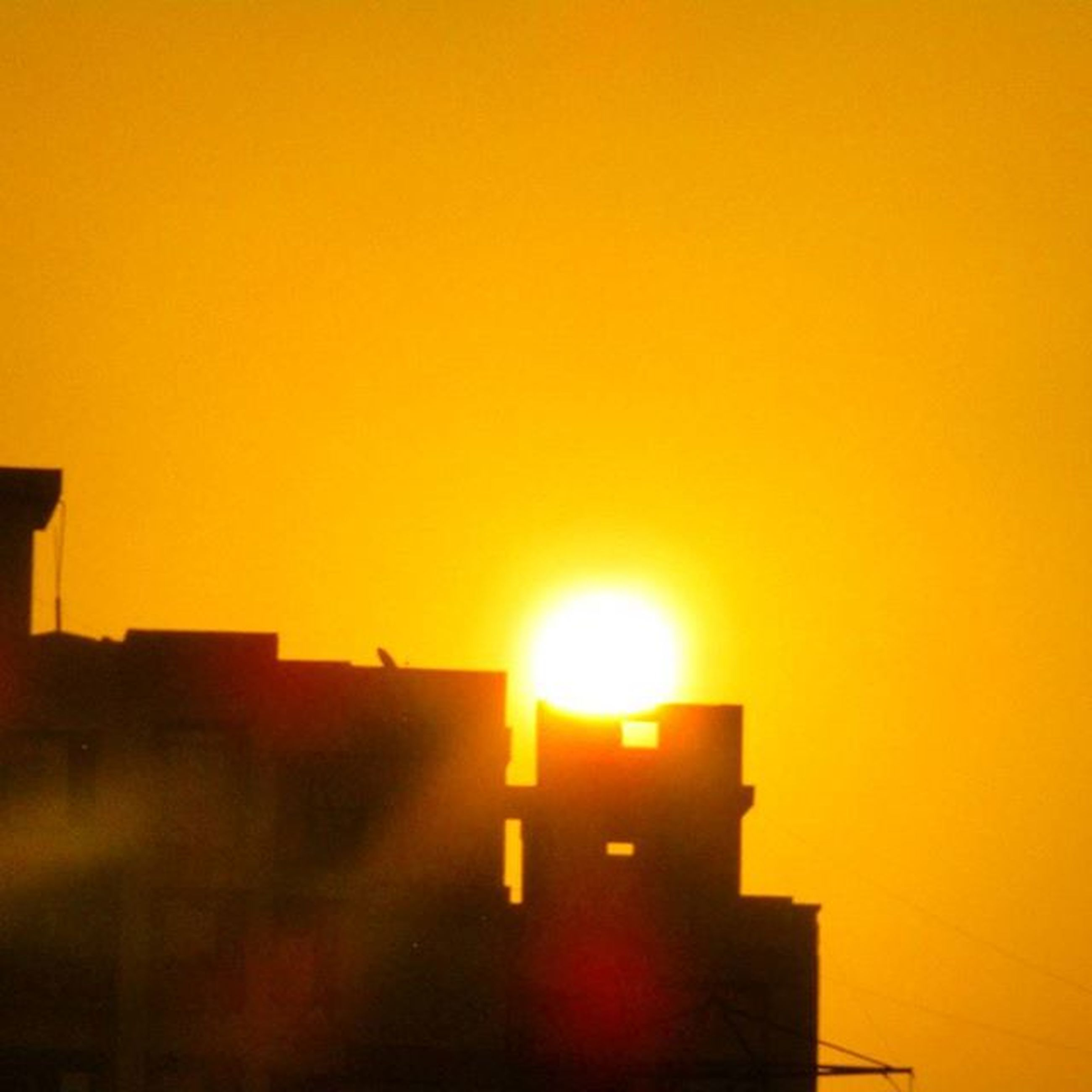 sunset, sun, building exterior, architecture, built structure, orange color, clear sky, copy space, sunlight, city, silhouette, sunbeam, lens flare, building, bright, residential building, outdoors, residential structure, no people, low angle view