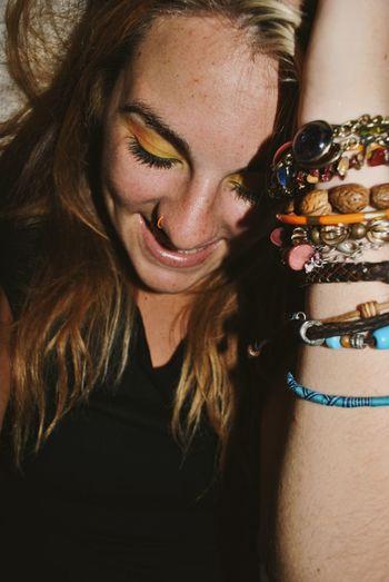 Close-up of beautiful woman wearing eye make-up and bracelets