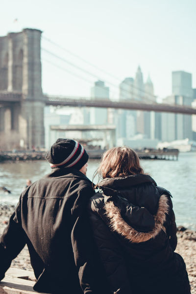 Architecture Backpack Bonding Bridge - Man Made Structure Building Exterior Built Structure Casual Clothing City City Life Connection Day Friendship Lifestyles Love Men Real People Rear View River Suspension Bridge Togetherness Travel Travel Destinations Two People Water Women
