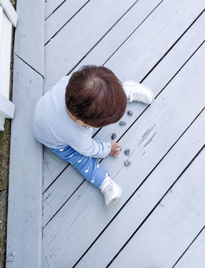 High angle view of boy sitting on wood