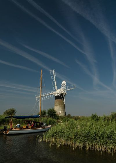 Norfolk Norfolk Broads Riverside Windmill Beauty In Nature Built Structure Cloud - Sky Contrails Day Fuel And Power Generation Grass Land Mode Of Transportation Nature Nautical Vessel No People Outdoors Plant River Sailboat Scenics - Nature Sky Transportation Water Waterfront