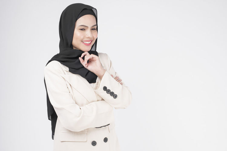 Smiling young woman standing against white background