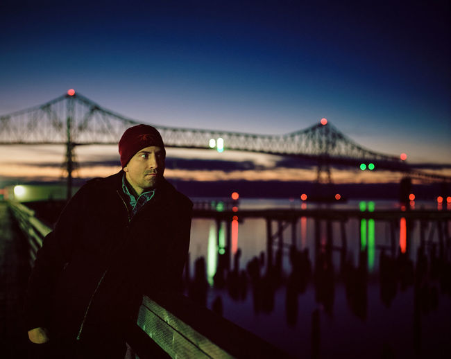 Man standing on bridge against clear sky at night