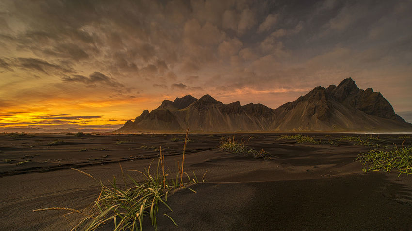 Vestrahorn, on the Stokksnes peninsula in Iceland, has dramatic peaks reaching up to 454 meters (1490 ft). It rises out of a flat, black sand beach and dominates the view whilst a gentle clear lagoon laps at the shore. Beauty In Nature Scenics - Nature Sky Sunset Cloud - Sky Tranquil Scene Tranquility Nature Land Idyllic Non-urban Scene No People Mountain Landscape Environment Orange Color Water Remote Mountain Range Outdoors Arid Climate Vestrahorn Vestrahorn Mountain Iceland Ancient Civilization