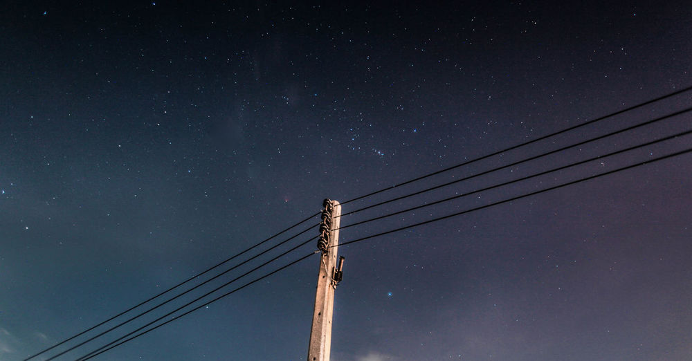 Low angle view of electricity pylon against sky at night