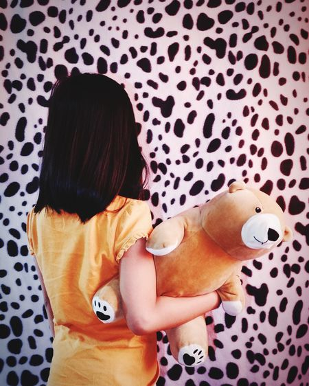 Rear view of girl holding stuffed toy by patterned wall