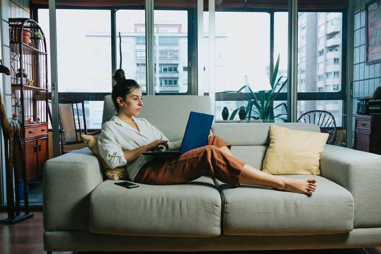 Woman using laptop while sitting on sofa at home
