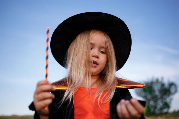 Portrait of cute girl holding hat against sky