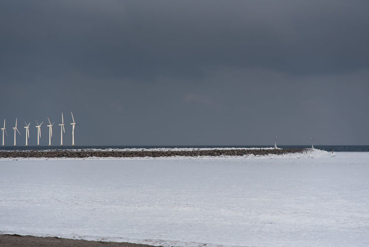 Windmills in a frozen landscape with dark skies, preparing for the future. Winter Denmark Scandinavia Ice Snow First Eyeem Photo Frozen Sea Sea No Swimming Sunset Copenhagen City Urban Ice Pattern Cold Nordic Boat Abstract Artistic Windmill Renewable Energy Green Energy Environment Future Vision