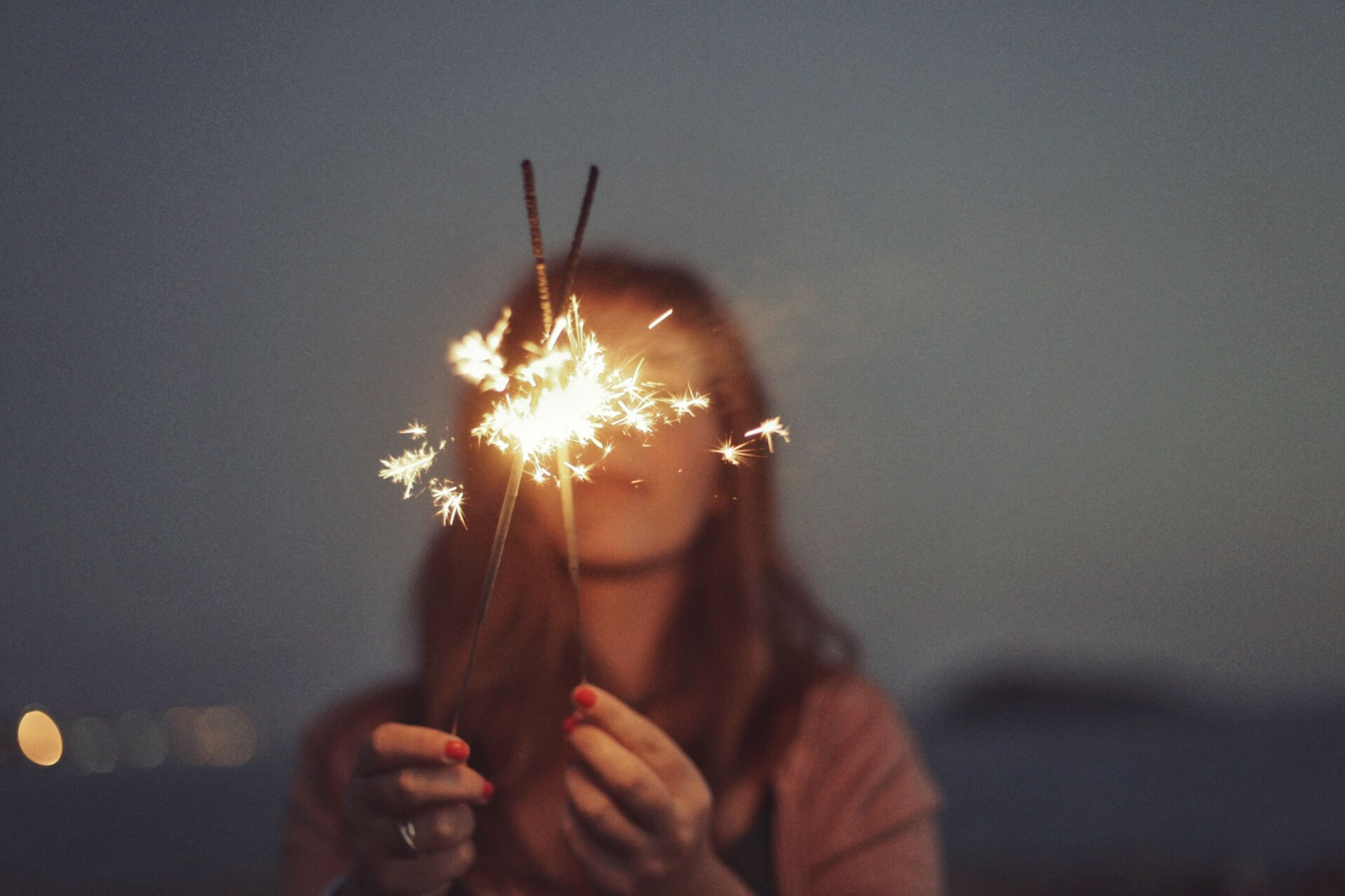 one person, firework, real people, illuminated, holding, leisure activity, burning, sparkler, lifestyles, headshot, celebration, motion, event, glowing, portrait, arts culture and entertainment, focus on foreground, firework display, front view, firework - man made object, sparks