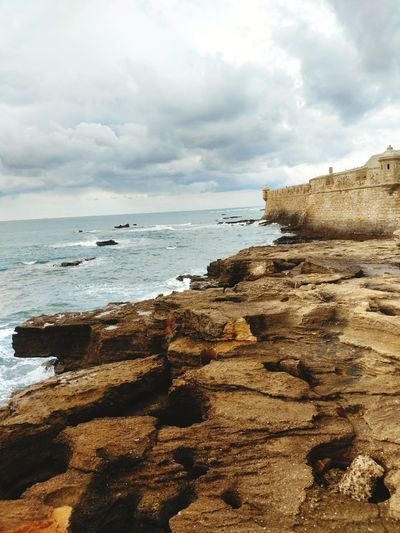 Rock - Object Nature Horizon Over Water Coastal Feature No People Sea Beach Outdoors Scenics Castillo San Sebastian Turistic Places SPAIN Streetphotography City Life Walking Around Lifestyle End Of Europe Atlantic Ocean Lonlyness Quiet Moments Cold Day Cadiz Architecturephotography Time Traveller History