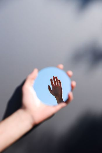 Reflection of hand against sky in mirror