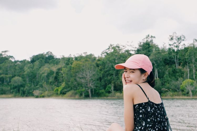 Portrait of young woman against lake and trees against sky
