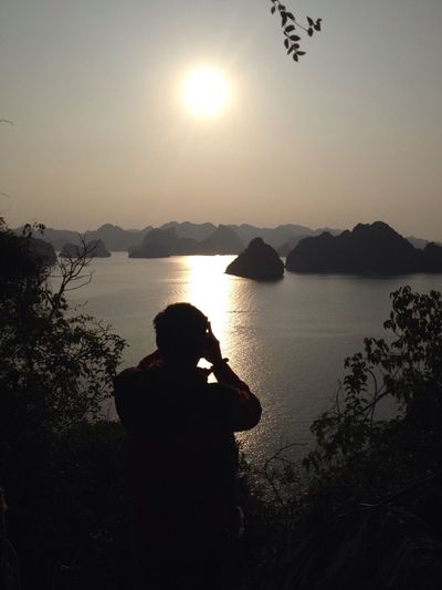 Rear view of silhouette man photographing against sea during sunset