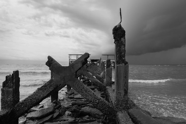 Abandoned built structure on beach against sky