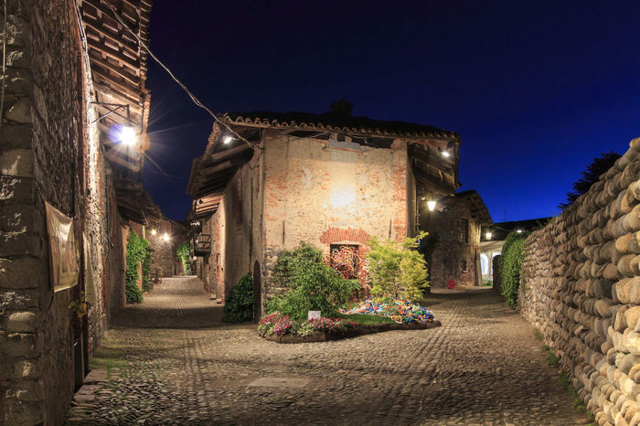 Candelo, Biella - May 4, 2016: View form the inside of the Medieval village of Ricetto di Candelo in Piedmont, used as a refuge in times of attack during the Middle Age. Alley Architecture Biella Blue Building Building Exterior Built Structure Candelo Candelo In Fiore City Diminishing Perspective Empty Illuminated Italy Medieval Village Night No People Outdoors Ricetto Di Candelo  Sky Street Light The Way Forward Vanishing Point Walkway